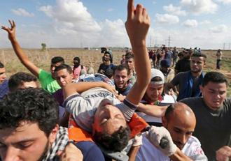 Protesters carry a wounded man injured by Israeli military attacks