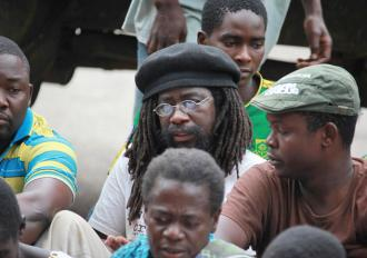 Munyaradzi Gwisai (center with glasses) sits with fellow activists outside a court house in Harare
