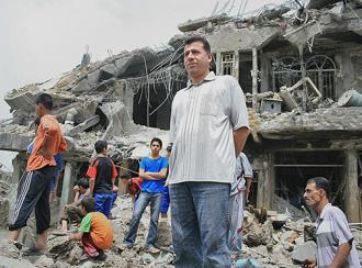 Iraqis in front of buildings demolished during U.S. attacks on Sadr City (Wissam Al-Okaili | AFP)