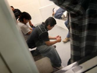 Detainees wait in a holding cell before being deported