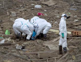 Worker sort through wreckage surrounding the Fukushima-Daiichi nuclear plant
