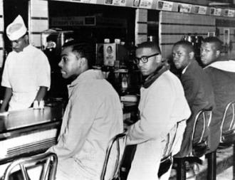 Four students sit at a lunch counter in defiance of segregation