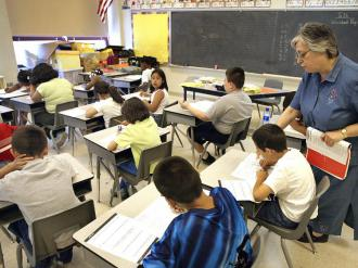 A teacher assists a student taking a test