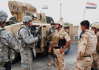 Iraqi officers talk to U.S. military advisors outside Mosul