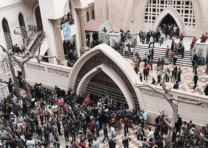 Worshippers fill the street outside a Coptic Christian church in Tanta after a deadly bomb attack
