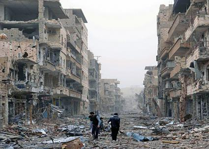 Syrian civilians walk through the rubble of the city of Deir ez-Zor