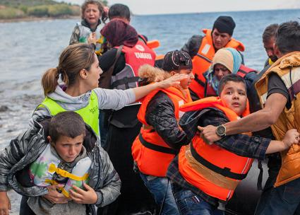 Syrian refugees are met by aid workers in Greece after crossing the Mediterranean (Ben White | flickr)