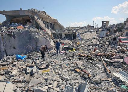 Civilians in Mosul search through the rubble left behind by a U.S. air strike