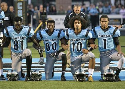 Lansing Catholic High School football players take a knee during the national anthem