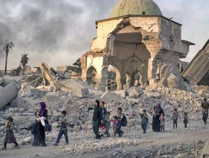 Civilians walk through the streets of Mosul after months of U.S. air strikes (Tasnim News | Wikimedia Commons)