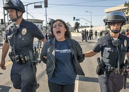 Immigrant rights activist Claudia Rueda is arrested during protests in Los Angeles
