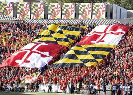 Giant Maryland flags in the stands at a UMD football game