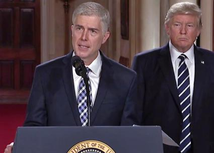 Neil Gorsuch speaks at a press conference while Trump looks on (White House)