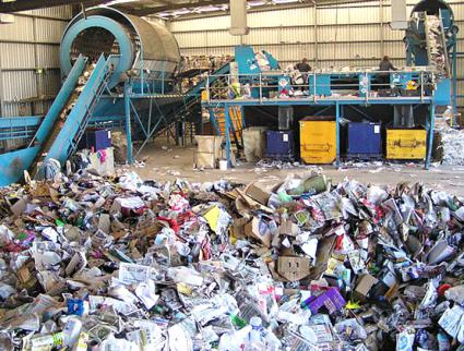 Workers process waste products at a Material Recycling Facility in Australia (Ropable | Wikimedia Commons)