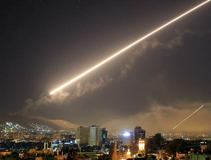 U.S. missiles streak across the sky over Damascus