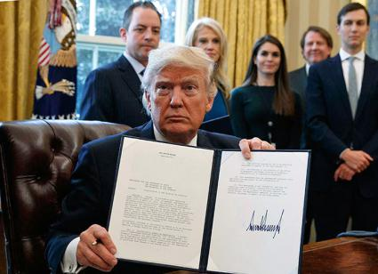 Trump displays his signature on an executive order in the Oval Office
