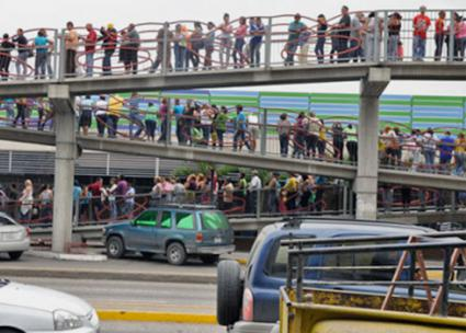 Customers line up for hours outside a supermarket in Caracas