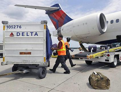 Baggage handlers load a passenger jet at Delta Air Lines
