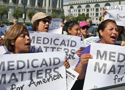 Protesters stand up against cuts in the Medicaid health program