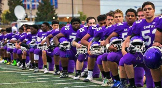 Seattle's Garfield High School football team kneels in protest during the national anthem
