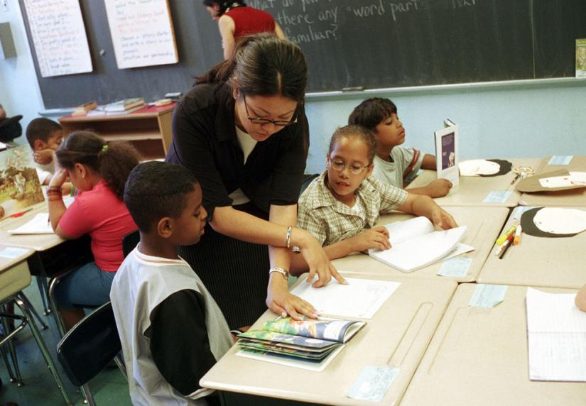 A teacher at P.S. 48 in Harlem works with students on reading skills