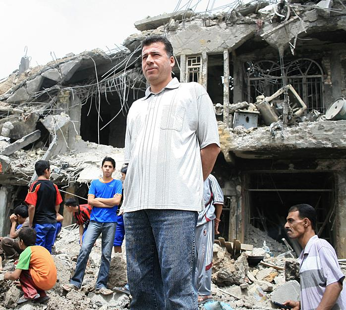 Iraqis in front of buildings demolished during U.S. attacks on Sadr City