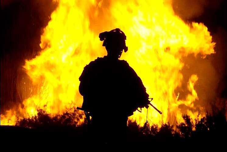 U.S. soldier looks on as occupation forces set vegetation on fire in Iraq