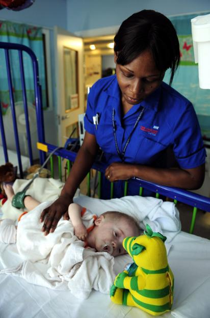A nurse cares for a seven-month-old at a National Health Service hospital in London