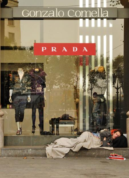 A homeless man rests outside a Prada store