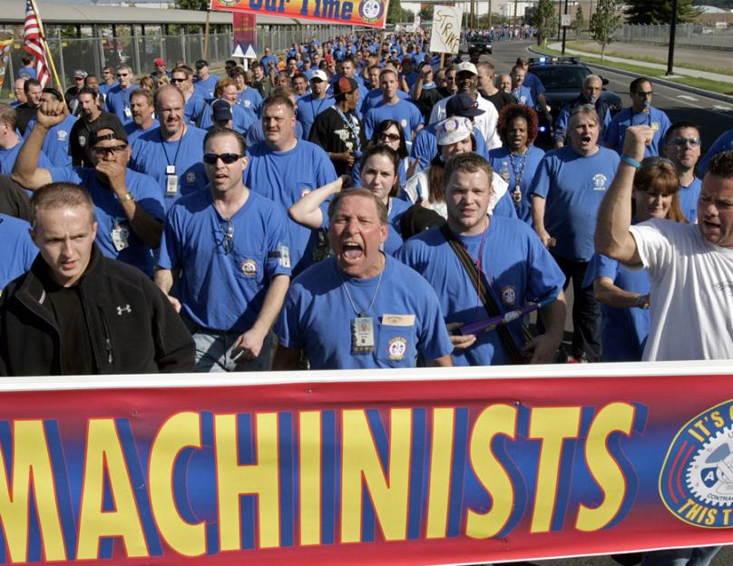 Boeing machinists march to their union hall to vote on the company's final contract offer