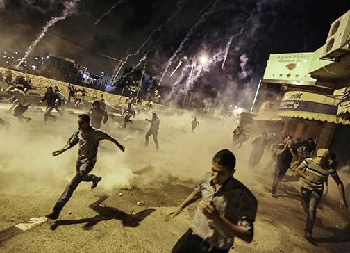 Palestinians in the West Bank run from an Israeli bombardment of tear gas