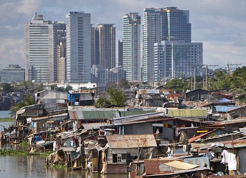 Slums in Manila with skyscrapers in the distance