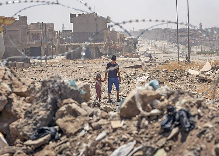 Children walk through the ruins of their neighborhood in Mosul