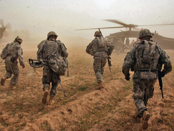U.S. soldiers run toward Black Hawk helicopters after a search for weapons caches in Iraq