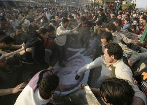 Protesters walk over a picture of Egyptian President Hosni Mubarak during a demonstration in Mahalla al-Kobra in April 2008