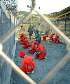 Detainees sit in a holding area at Camp X-Ray at the U.S. Naval Base in Guantánamo Bay, Cuba, on January 11, 2002.