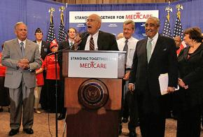 Rep. John Dingell speaks, surrounded by fellow Democrats, after George Bush's veto of Medicare legislation was overridden by Congress