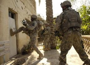 U.S. soldiers kick in the door of a building in Buhriz, Iraq
