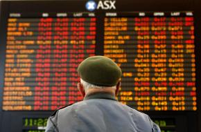 A man looks up at stock prices on the Australian stock market