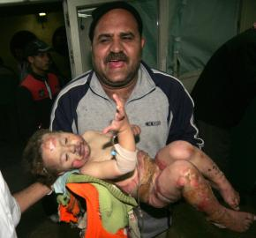 A Palestinian father carries his wounded baby daughter into a hospital in Gaza City