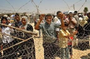 Palestinians wait behind barbed wire at the checkpoint at Rafah