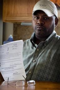 A man in Nevada holds up part of the paperwork he has filed in an effort to secure his right to vote