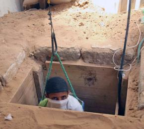 A Palestinian worker is lowered into a tunnel between Gaza and Egypt.
