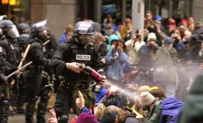 Peaceful protesters sit in as riot police fire pepper spray during the 1999 WTO protests