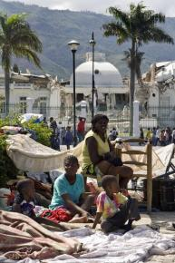 A family of earthquake survivors rests in an encampment facing the collapsed Presidential Palace
