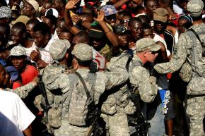 U.S. troops push back a crowd of Haitians waiting for food and water outside the Port-au-Prince airport