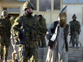 U.S. troops transport an Afghan detainee