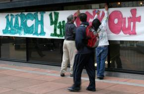 Activists post a banner for the March 4 Day of Action at Laney College in Oakland