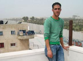 Bilal Jadou inside the Aida refugee camp, overlooking the separation wall and his home on the other side