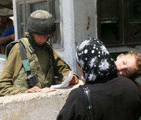 An IDF soldier examines a Palestinian woman's papers at the Beit Iba checkpoint outside Nablus in the West Bank